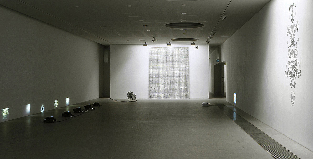 installation view from the exhibition Visitor, 5 slide projections. Disturbance, electrical fan and panel made of veneer and white pvc sequins. The first sigh, video projector, DVD. Mnemonic I, wall ornament made with hand cut stickers.