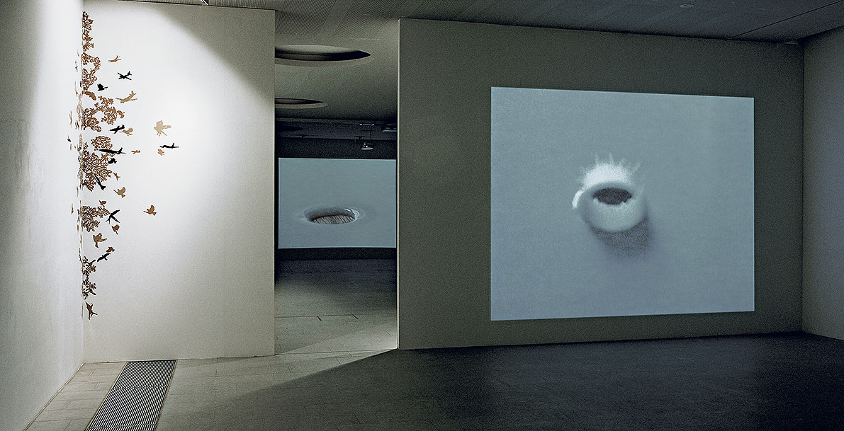 Installation view of the exhibition, Mnemonic II, hand cut sticker ornament on wall, The spirit of the snail (milk), video projection, Tear gravity (milk), video projection