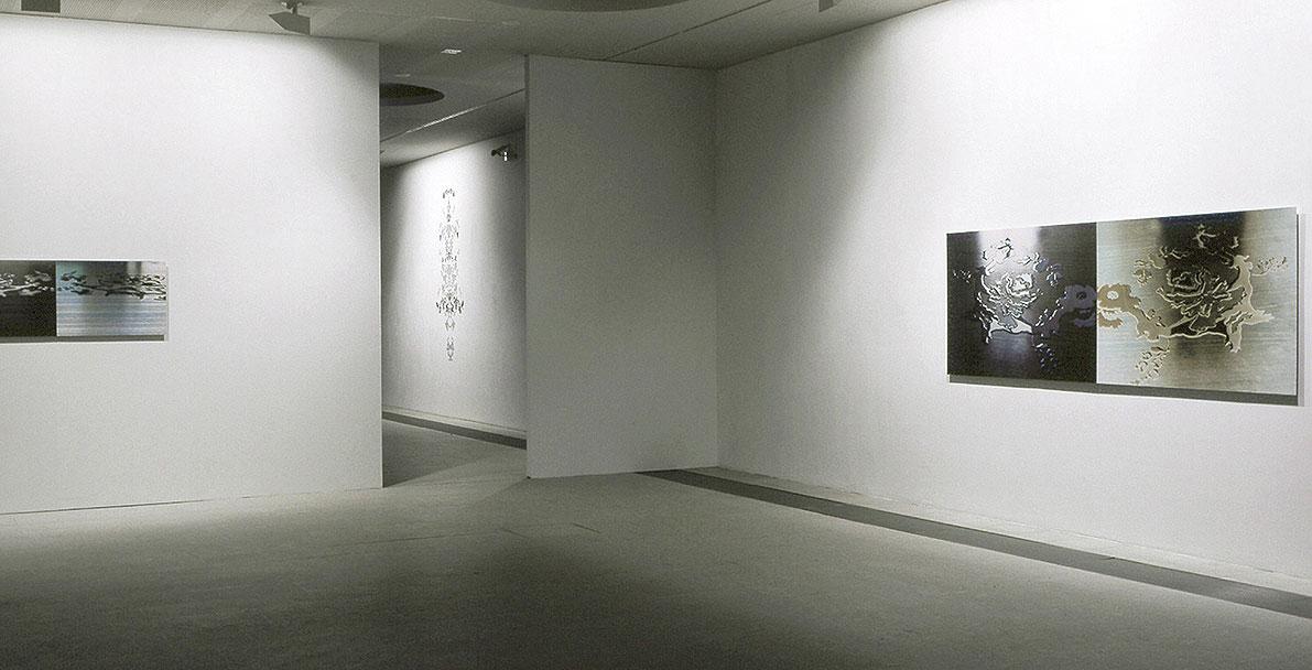 Installation view of the exhibition, Replica III, two c-prints on aluminium, Mnemonic I, hand cut sticker ornament on wall: Replica I, two c-prints on aluminium
